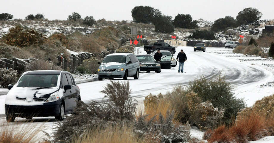 Cars slide on Paseo del Norte Sunday, Nov.24, 2013, in Albuquerque, N.M., after a winter storm hit New Mexico over the weekend making driving difficult for drivers. A large storm already blamed for at least eight deaths in the West slogged through Oklahoma, Texas, New Mexico and other parts of the southwest Sunday as it slowly churned east ahead of Thanksgiving.(AP PhotosAlbuquerque Journal, Jim Thompson) THE SANTA FE NEW MEXICAN OUT / Albuquerque Journal