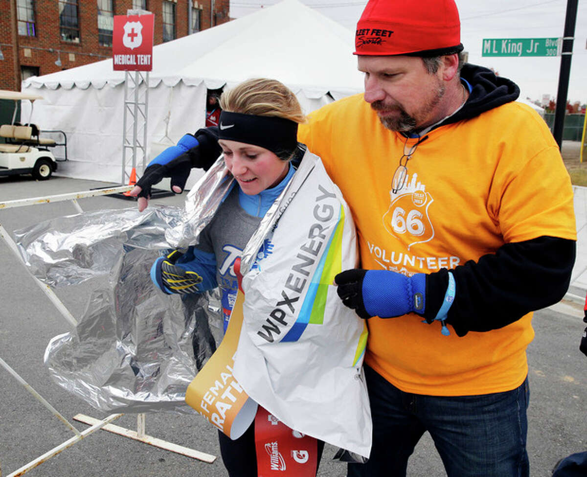 Natasha Cockram, first place female finisher in the half-marathon, gets covered with a mylar blanket by a volunteer after crossing the finish line of the Route 66 Marathon at Guthrie Green in Tulsa, Okla., Sunday, Nov. 24, 2013. A large storm already blamed for at least eight deaths in the West slogged through Oklahoma, Texas, New Mexico and other parts of the Southwest on Sunday, leading to hundreds of flight cancellations as it slowly churned east ahead of Thanksgiving. (AP Photo/Tulsa World, Michael Wyke)