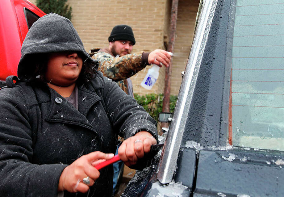 Samantha Hernandez scrapes ice off of the windows after Kenneth Fields sprays them with a concoction of vinegar and water to soften the ice on Saturday, Nov. 23, 2013, in Odessa, Texas. The fierce weather has caused at least eight deaths and prompted advisories Saturday afternoon in New Mexico and Texas. (AP Photo/The Odessa American, Edyta Blaszczyk) / Odessa American