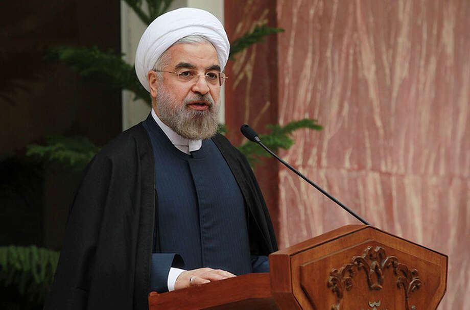 In this photo released by the official website of the office of the Iranian Presidency, Iran's President Hassan Rouhani speaks during a news briefing after Iran and world powers agree in Geneva to a deal over Iran's nuclear program, at the Presidency compound in Tehran, Iran, Sunday, Nov. 24, 2013. Iran struck a deal with the U.S. and five other world powers, agreeing to a temporary freeze of its nuclear program in the most significant agreement between Washington and Tehran in more than three decades. The deal commits Iran to curb its nuclear activities for six months in exchange for limited sanctions relief. (AP Photo/Presidency Office, Mohammad Berno) / Iranian Presidency Office