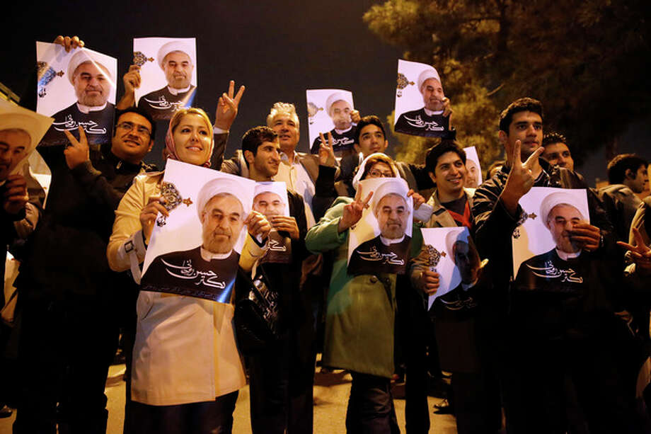 In this photo released by the Iranian Students News Agency, ISNA, Iranians hold posters of President Hassan Rouhani as they welcome Iranian nuclear negotiators upon their arrival from Geneva at the Mehrabad airport in Tehran, Iran, Sunday, Nov. 24, 2013. Hundreds of cheering supporters greeted Iran's nuclear negotiators as they arrived back to Tehran late Sunday night. Tehran agreed Sunday to a six-month pause of its nuclear program while diplomats continue talks. International observers are set to monitor Iran's nuclear sites as the West eases about $7 billion of the economic sanctions crippling the Islamic Republic. (AP Photo/ISNA,Hemmat Khahi) / Iranian Students News Agency, ISNA