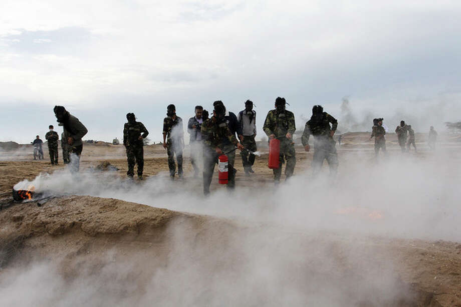 In this picture released by Tasnim News Agency on Wednesday, Nov. 20, 2013, members of Iran's paramilitary Basij force, which is controlled by the Revolutionary Guard, attend a maneuver of preparation for possible attack on Iran's nuclear sites, by the nuclear power plant in Bushehr, southern Iran. (AP Photo/Tasnim, Hosein Heydarpour) / Tasnim News Agency