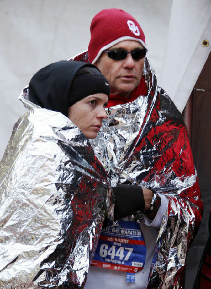 Ashely Bartell and her dad Mitch Gregory huddle under mylar blankets to stay warm before the start of the Route 66 Marathon in Tulsa, Okla., Sunday, Nov. 24, 2013. A large storm already blamed for at least eight deaths in the West slogged through Oklahoma, Texas, New Mexico and other parts of the Southwest on Sunday, leading to hundreds of flight cancellations as it slowly churned east ahead of Thanksgiving. (AP Photo/Tulsa World, Michael Wyke)