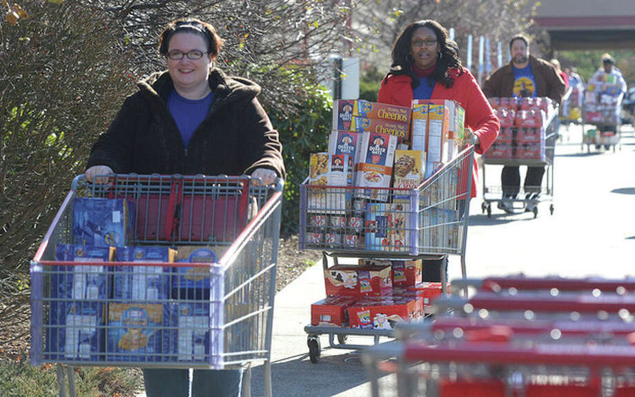 Hour Photo/Alex von Kleydorff. Priceline.com employees push carriages full of food from Costco to waiting trucks to be delivered to the CT Food bank
