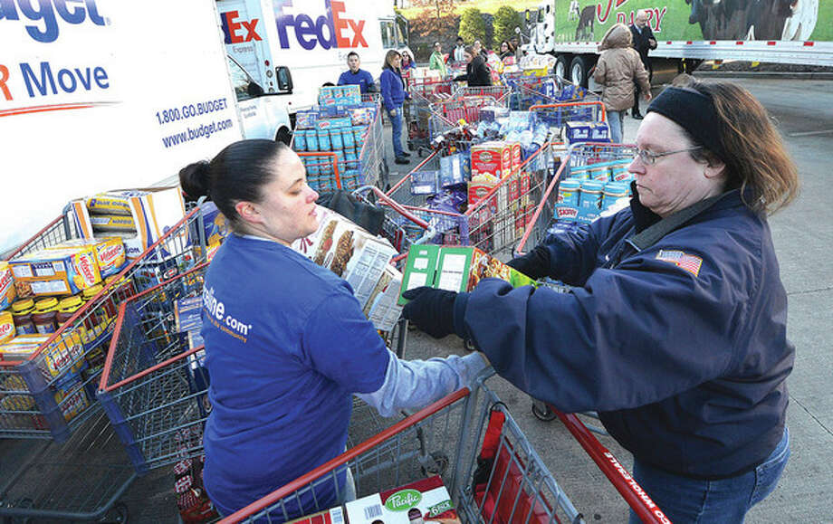 Hour Photo/Alex von Kleydorff . Priceline.com employees Stacey Kurtika and Karen Tappe pass donated groceries from carts to other employees passsing it into trucks at Costco