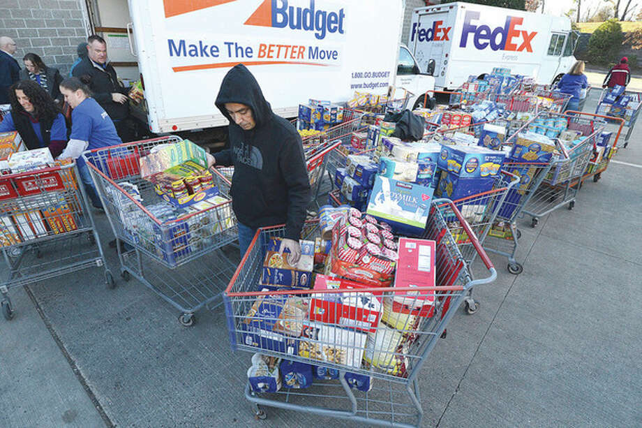 Hour Photo/Alex von Kleydorff . Priceline.com employee Lyndon rego pulls his cart to the front of the line as they are unloaded into trucks at Costco in Norwalk
