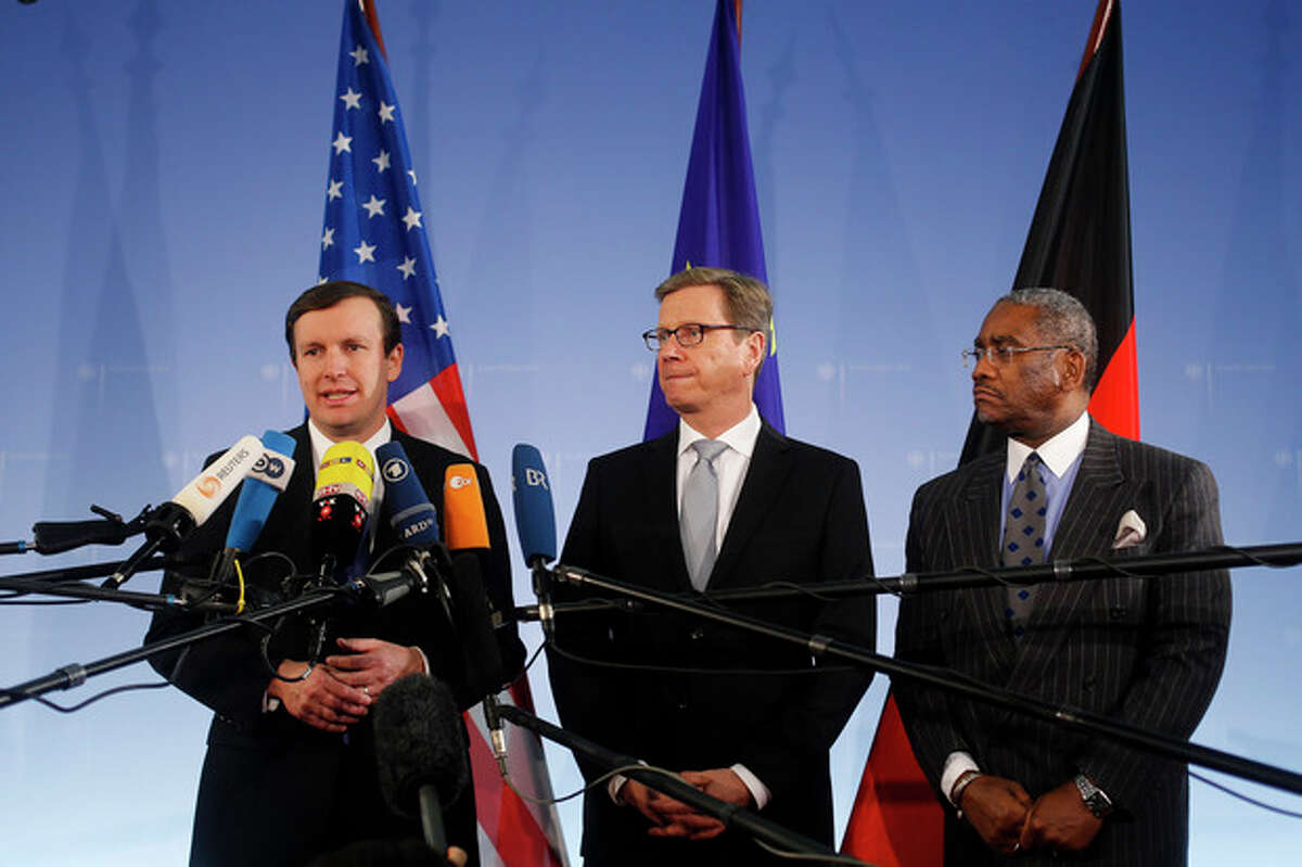 Sen. Christopher Murphy, left, a Connecticut Democrat who serves on the Senate Foreign Relations Committee, briefs the media prior to a meeting with Congressman Gregory Meeks, right, and German Foreign Minister Guido Westerwelle, center, at the foreign ministry in Berlin, Monday, Nov. 26, 2013. Following allegations of massive National Security Agency surveillance, the politicians will discuss the relationship between the two countries and how to restore trust to trans-Atlantic ties. (AP Photo/Markus Schreiber)