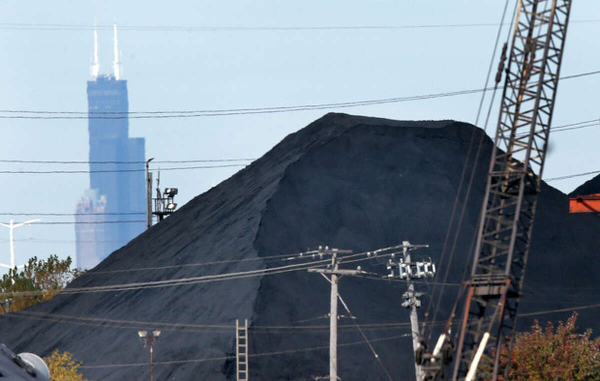 In this Oct. 25, 2013 photo, the Willis Tower in downtown Chicago provides a backdrop to a huge mound of petroleum coke, or pet coke, in the a residential area southeast part of the city. An increasing volume and size of petcoke piles is causing environmental concerns for residents in this working-class neighborhood. (AP Photo/Charles Rex Arbogast)