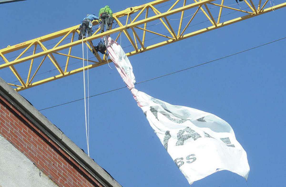 Protesters bring up their banner that they hung from the contstruction crane at the site of 66 Summer Street in Stamford monday morning. The protest was againtst UBS in Stamford and thier support of mountain top construction in Appalachia. Hour photo/Matthew Vinci