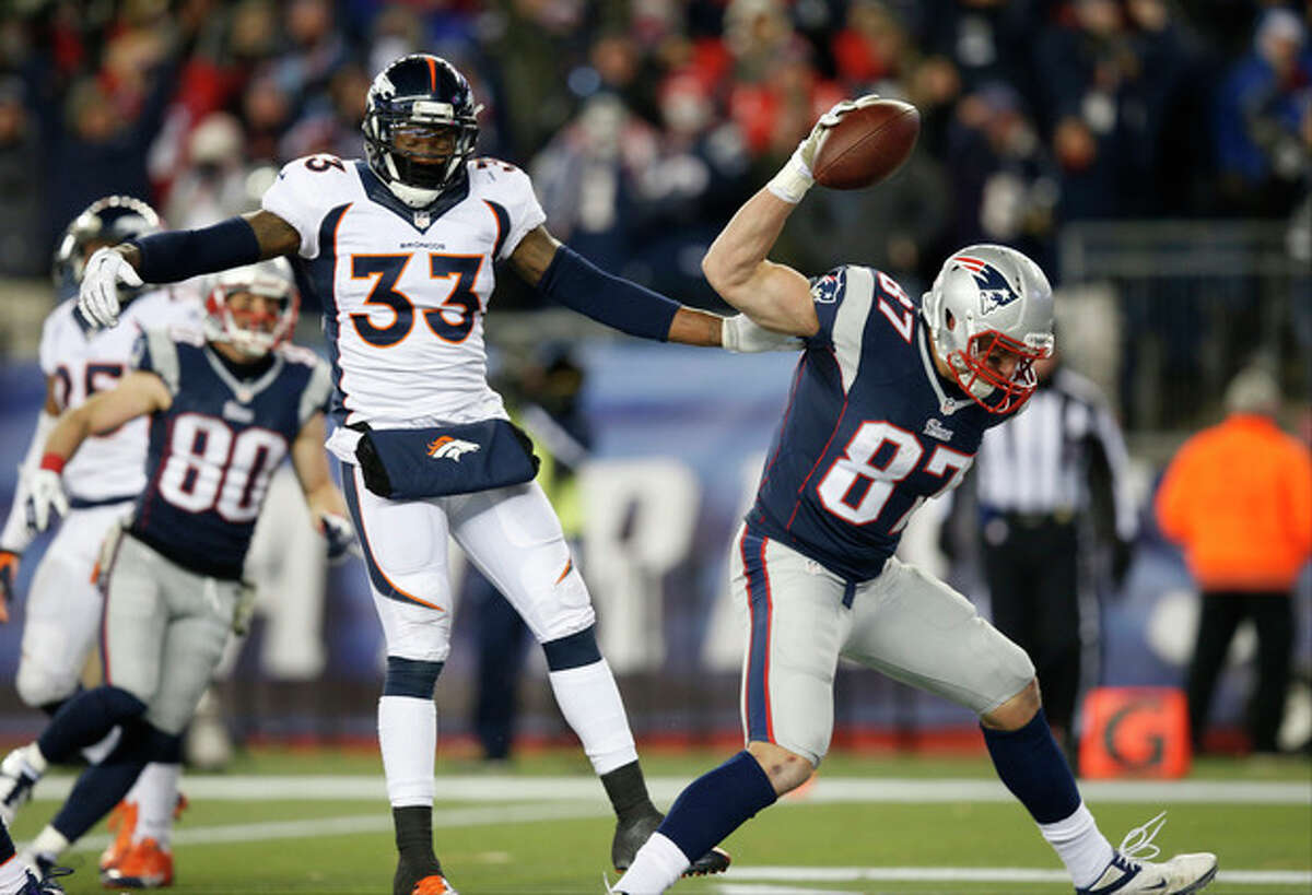 New England Patriots tight end Rob Gronkowski (87) celebrates his touchdown in front of Denver Broncos safety Duke Ihenacho (33) in the third quarter of an NFL football game Sunday, Nov. 24, 2013, in Foxborough, Mass. (AP Photo/Elise Amendola)