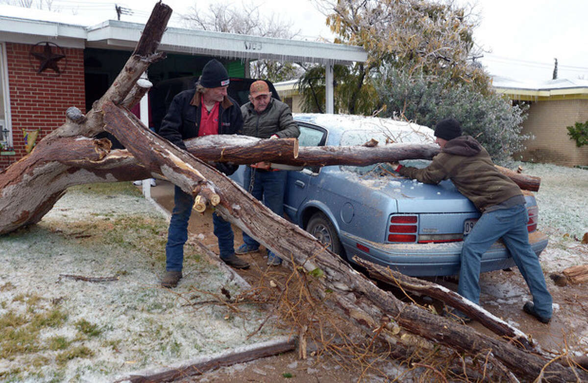 Workers with Duncan Tree Service remove a tree that fell Sunday on Jack Sullivan's Cutlass parked in the driveway of his Odessa, Texas home, on Monday, Nov. 25, 2013. Wintry weather with freezing rain, sleet and snow swept through much of West Texas over the weekend, causing power outages and many tree limbs to break under the weight of the ice. Conditions are forecast to improve during the next couple of days. (AP Photo/Odessa American, Mark Sterkel)