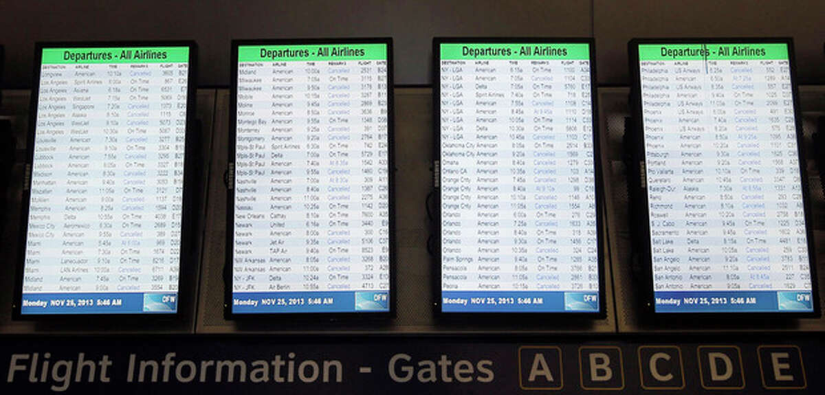 Departure boards display dozens of canceled flights in terminal D at Dallas-Fort Worth International airport, Monday, Nov. 25, 2013. Winter weather has caused travel disruptions throughout the area. (AP Photo/Brandon Wade)