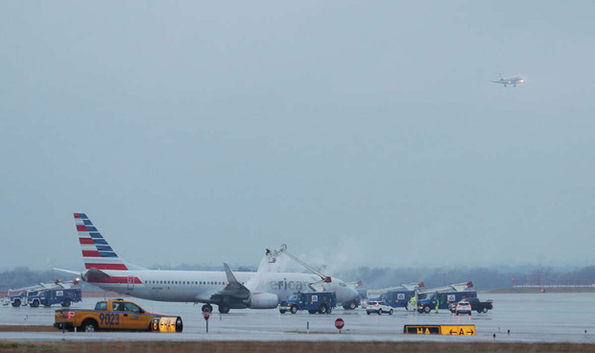 Crews spray deicing solution onto an American Airlines 737 before departure at Dallas-Fort Worth International airport, Monday, Nov. 25, 2013. Winter weather has caused travel disruptions throughout the area including the cancelation and delays of hundreds of flights. (AP Photo/Brandon Wade)