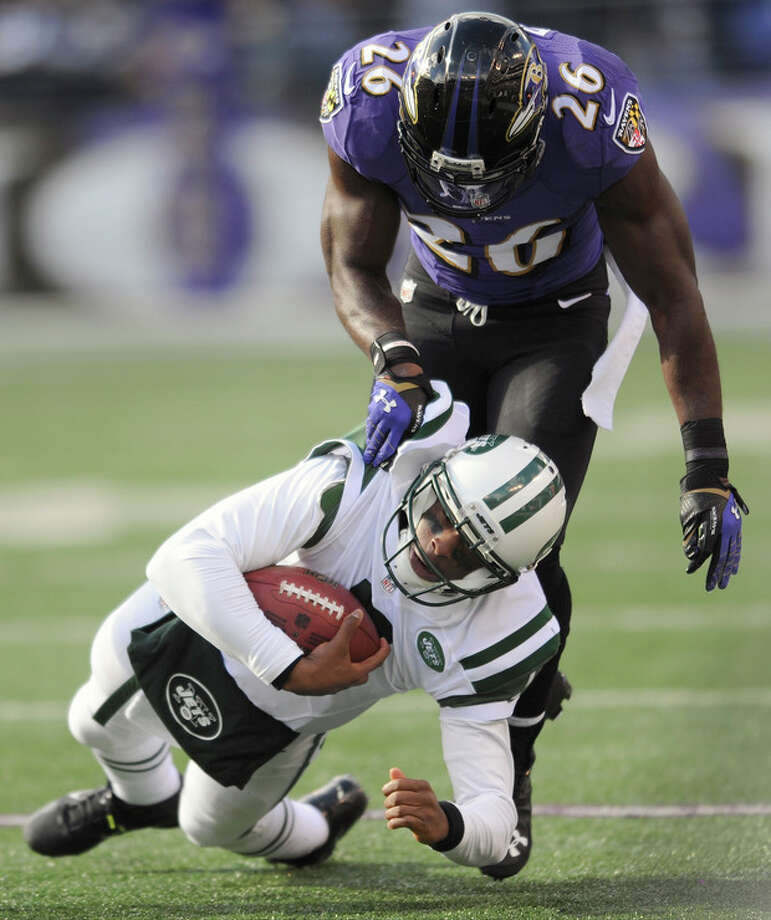 Baltimore Ravens free safety Matt Elam, top, sacks New York Jets quarterback Geno Smith during the first half of an NFL football game in Baltimore, Sunday, Nov. 24, 2013. (AP Photo/Gail Burton) / FR4095 AP