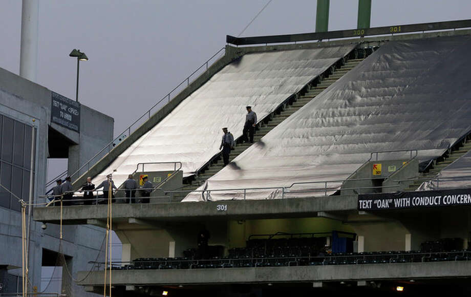Law enforcement officials walk in the upper deck of O.co Coliseum after an NFL football game between the Oakland Raiders and the Tennessee Titans in Oakland, Calif., Sunday, Nov. 24, 2013. Authorities say a football fan jumped after the game from the third deck of the Oakland Coliseum, injuring herself and a man one level below who tried to catch her. She and the man who tried to catch her were rushed to the hospital for treatment. (AP Photo/Jeff Chiu) / AP