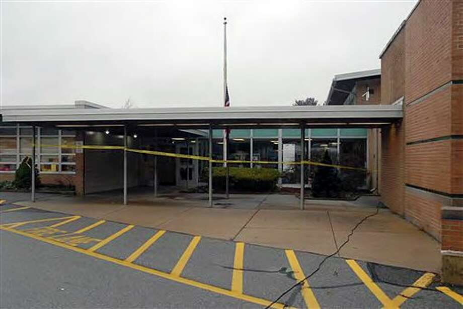 """This image contained in the """"Appendix to Report on the Shootings at Sandy Hook Elementary School and 36 Yogananda St., Newtown, Connecticut On December 14, 2012"""" and released Monday, Nov. 25, 2013, by the Danbury, Conn., State's Attorney shows a scene outside the entrance to Sandy Hook Elementary School in Newtown, Conn. Adam Lanza opened fire inside the school killing 20 first-graders and six educators before killing himself as police arrived. (AP Photo/Office of the Connecticut State's Attorney Judicial District of Danbury) / Office of the Connecticut State's Attorney Judicial District of"""