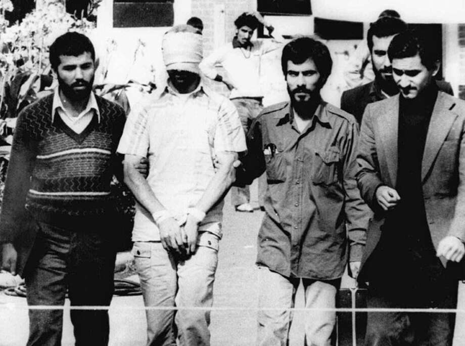 FILE - In this Nov. 9, 1979, file photo, one of the hostages being held at the U.S. Embassy in Tehran is displayed to the crowd, blindfolded and with his hands bound, outside the embassy. Fifty-two of the hostages endured 444 days of captivity. Former Iranian hostages had varied reactions to the news of the nuclear deal between the U.S. and Iran in what is being billed as a trust-building agreement designed to yield a more comprehensive deal six months from now. (AP Photo/File) / AP