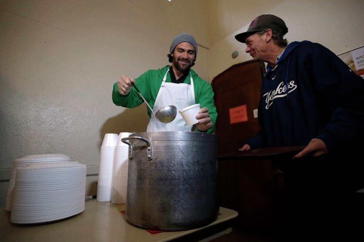 New York Jets NFL football quarterback Mark Sanchez, left, pours a bowl of soup for William Day, 52, during a visit to the Community Soup Kitchen of Morristown as part of the team's Thanksgiving Day week celebration, Tuesday, Nov. 26, 2013, in Morristown, N.J. (AP Photo/Julio Cortez)