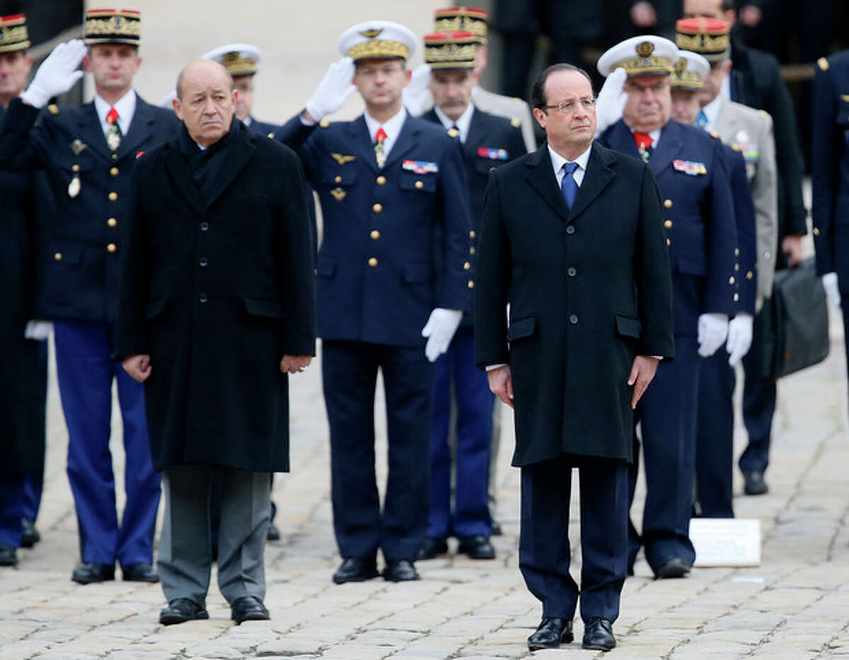 French President Francois Hollande, right, and Defense Minister Jean-Yves Le Drian reviews the troops during a military ceremony, Tuesday, Nov. 26, 2013, at the Invalides in Paris. France will send 1,000 troops to Central African Republic under an expected U.N.-backed mission to keep growing chaos at bay, the defense minister said Tuesday ?- boosting the French military presence in Africa for the second time this year. (AP Photo/Patrick Kovarik, Pool)