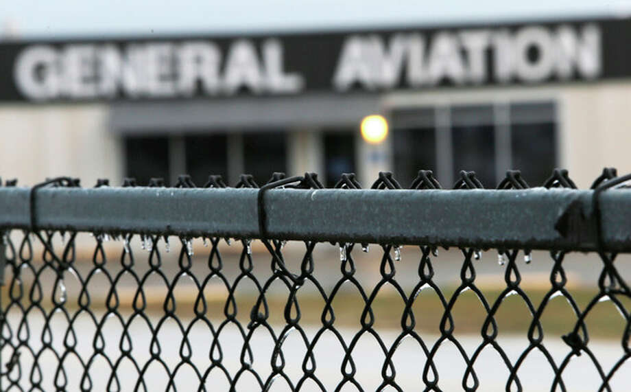 Icicles form on a chain link fence outside of the old general aviation building at Dallas-Fort Worth International airport, Monday, Nov. 25, 2013. Winter weather has caused travel disruptions throughout the area including the cancelation and delays of hundreds of flights. (AP Photo/Brandon Wade) / FR168019 AP