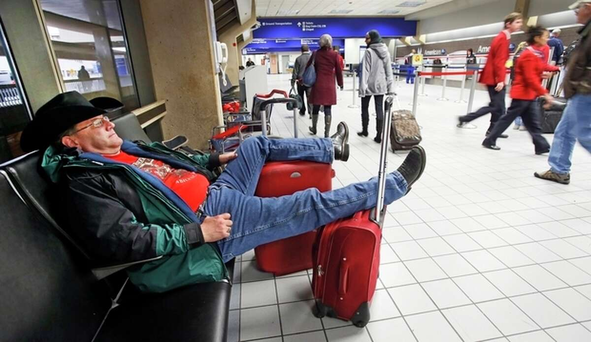 David McCain of Abilene relaxes in the seats of the ticketing area for American airlines in Terminal C after his flight home to Abilene was canceled, as an arctic cold front begins to move into the North Texas area on Sunday, Nov. 24, 2013. (AP Photo/Dallas Morning News, Louis DeLuca)