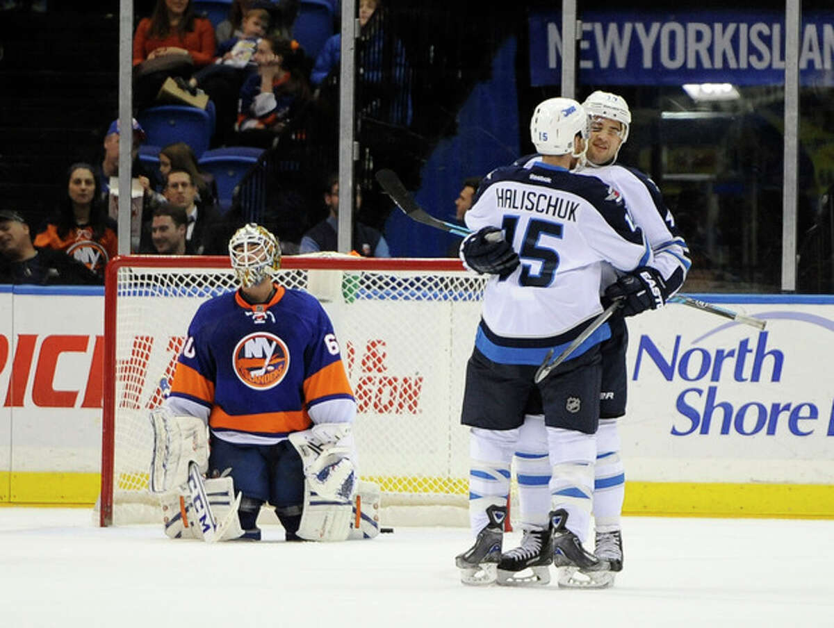 New York Islanders goalie Kevin Poulin (60) reacts as Winnipeg Jets' Devin Setoguchi celebrates his goal with Matt Halischuk (15) in the second period of an NHL hockey game on Wednesday, Nov. 27, 2013, in Uniondale, N.Y. (AP Photo/Kathy Kmonicek)