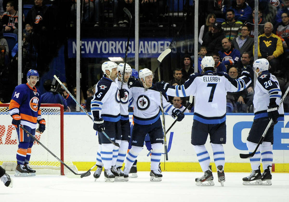 New York Islanders' Thomas Hickey (14) watches Winnipeg Jets' Andrew Ladd (16), second from left, celebrates his goal with teammates in the second period of an NHL hockey game on Wednesday, Nov. 27, 2013, in Uniondale, N.Y. (AP Photo/Kathy Kmonicek)