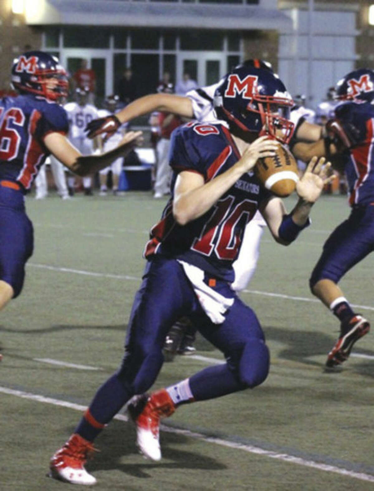 Contributed photo Former Brien McMahon quarterback Trey Newcomb looks for a receiver during a 2012 game. Newcomb was forced to give up football after suffering a serious injury during a game but is adapting nicely.