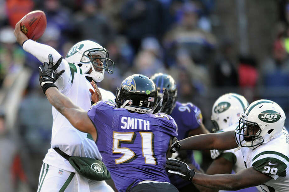 New York Jets quarterback Geno Smith, left, passes the ball under pressure from Baltimore Ravens inside linebacker Daryl Smith (51) during the first half of an NFL football game in Baltimore, Md., Sunday, Nov. 24, 2013. (AP Photo/Gail Burton) / FR4095 AP