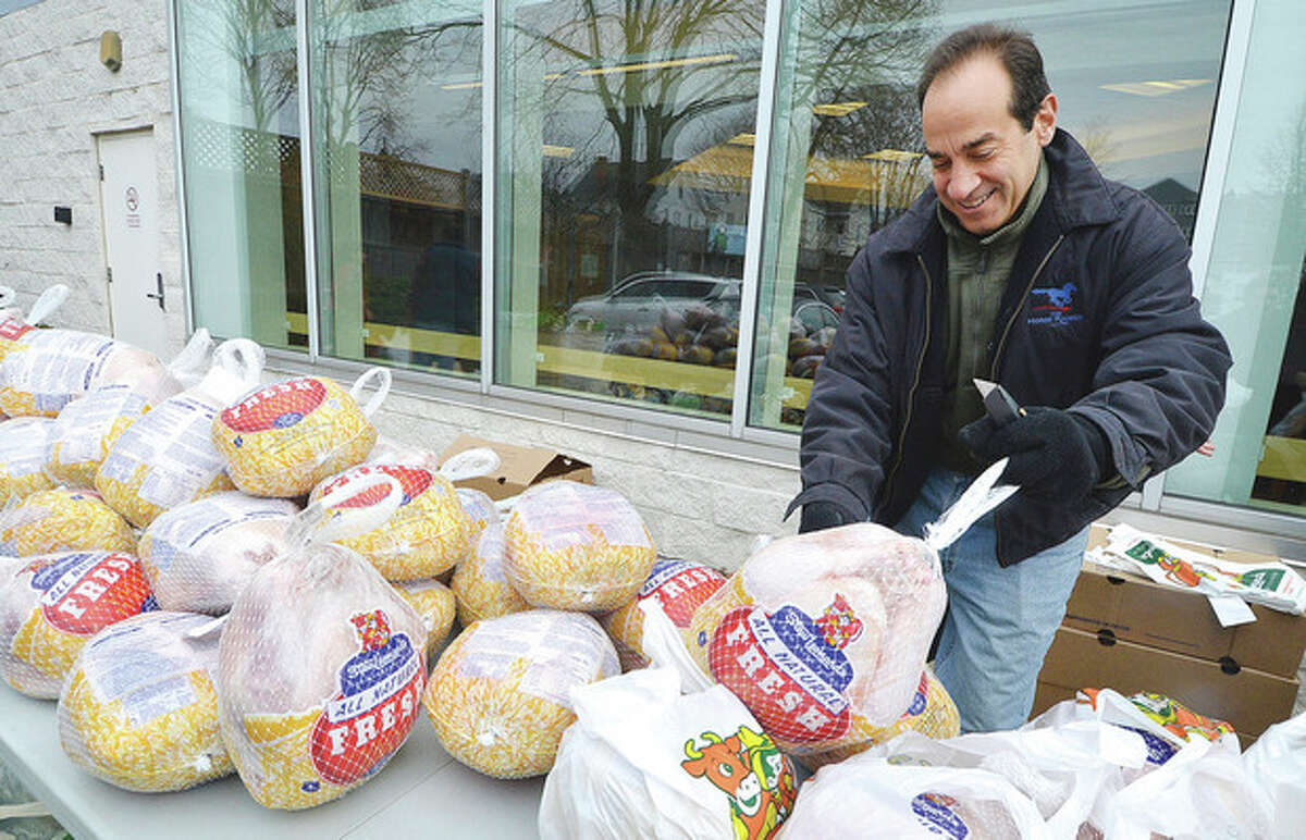 Hour Photo/Alex von Kleydorff Jesse Fink with Millstone Farm in Wilton places some turkeys from boxes onto a table for distribution to families in need at the Norwalk Community Health Center on Tuesday.