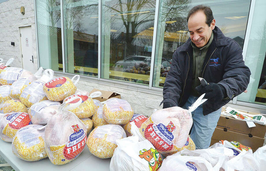 Hour Photo/Alex von KleydorffJesse Fink with Millstone Farm in Wilton places some turkeys from boxes onto a table for distribution to families in need at the Norwalk Community Health Center on Tuesday.