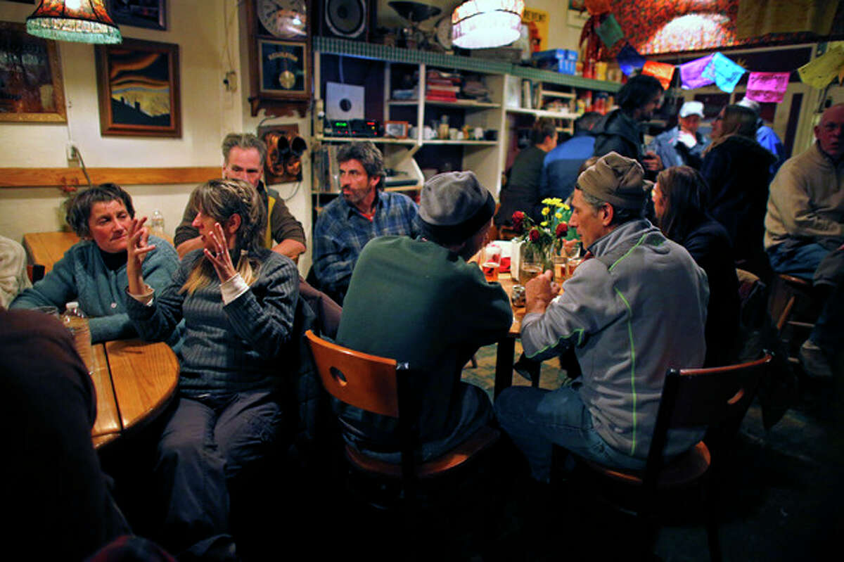 In this Nov. 23, 2013 photo, groups pack around tables talking inside The Merc, a locally-popular bar and restaurant which remains open on Saturday nights despite September's destructive flood, in the Rocky Mountain town of Jamestown, Colo. For a few precious hours every Saturday night, Jamestown looks more like it did before floods and mudslides destroyed a fifth of its homes. Those who stayed and those who fled to rental homes in the nearby Boulder area return to the Jamestown Mercantile, the town?'s meeting place for over 100 years, to share a dinner, then push back the tables and dance to live music. (AP Photo/Brennan Linsley)