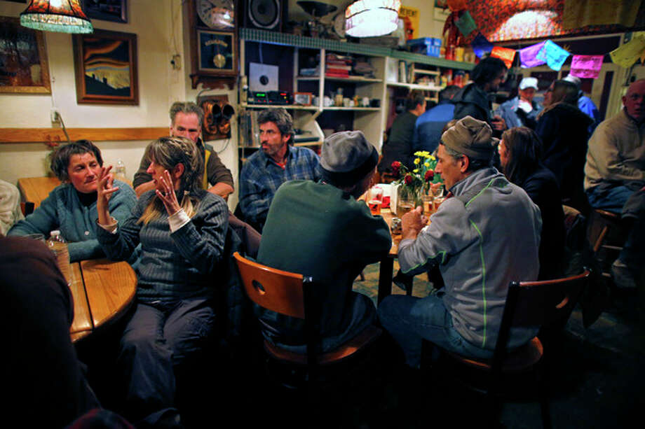 In this Nov. 23, 2013 photo, groups pack around tables talking inside The Merc, a locally-popular bar and restaurant which remains open on Saturday nights despite September's destructive flood, in the Rocky Mountain town of Jamestown, Colo. For a few precious hours every Saturday night, Jamestown looks more like it did before floods and mudslides destroyed a fifth of its homes. Those who stayed and those who fled to rental homes in the nearby Boulder area return to the Jamestown Mercantile, the town's meeting place for over 100 years, to share a dinner, then push back the tables and dance to live music. (AP Photo/Brennan Linsley) / AP