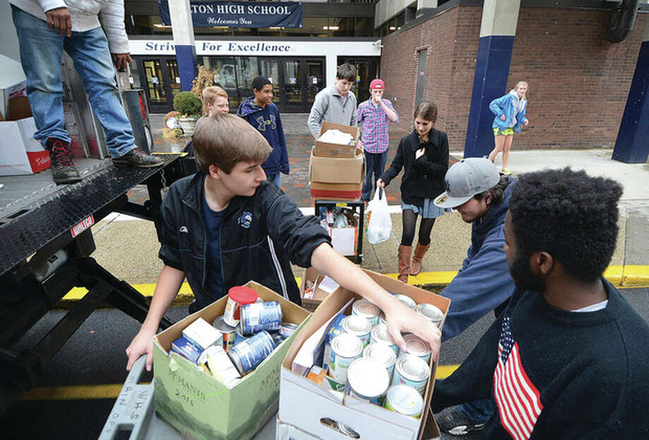 Hour Photo/Alex von Kleydorff Tyler Christensen holds steady boxes of canned food as students help stack more collected food on the truck lift for The Fairfield County Food Bank