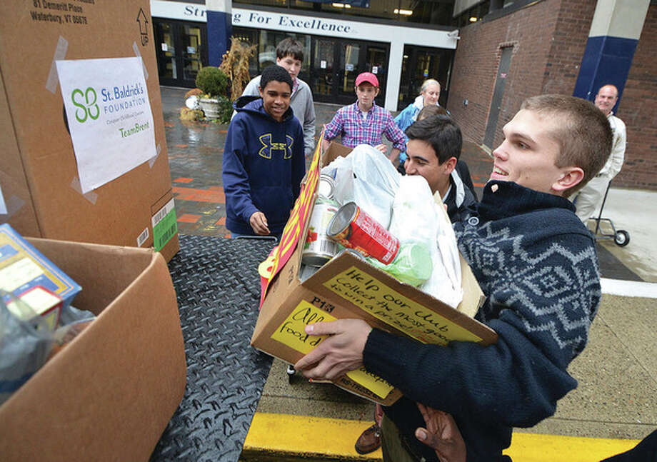 Hour Photo/Alex von KleydorffAlex Bendix lifts onto the truck a heavy box of canned goods collected by student clubs to donate to the Lower Fairfield County Food Bank.