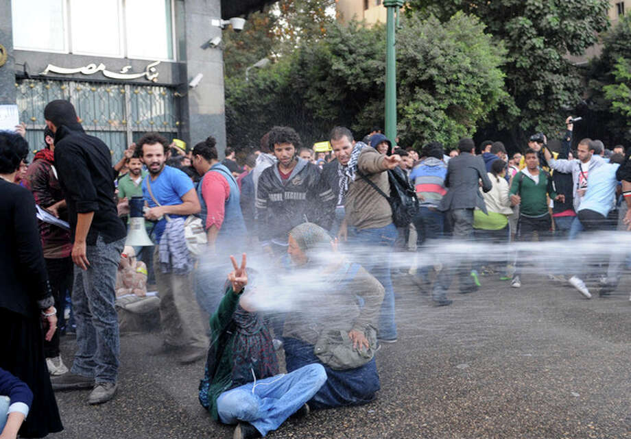 FILE - In this Tuesday, Nov. 26, 2013 file photo, Egyptian police fire water cannons to disperse a protest by secular anti-government activists in Cairo, the security forces' first implementation of a controversial new law forbidding protests held without a permit from authorities. After being detained at a Cairo protest, the 14 women, some of Egypt's most prominent democracy advocates, were beaten, pulled by the hair and piled into a police van, taken on a sinister nighttime ride through the desert where they were finally dumped by the road, the women recount. The abuse, reminiscent of the Hosni Mubarak era, points to how Egypt's new military-backed authorities are becoming bolder in silencing dissent, exploiting the fight against Islamists and divisions among secular activists. (AP Photo/Mohammed Asad, File) / AP