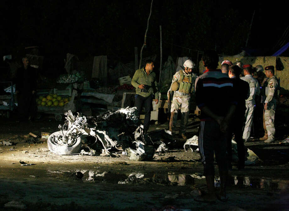 Civilians and security forces inspect the site of a double car bomb attack at a vegetable market in the Shiite holy city of Najaf, 100 miles (160 kilometers) south of Baghdad, Iraq, Thursday, Nov. 28, 2013. Officials in Iraq say attacks across Iraq killed tens of people Thursday. (AP Photo/Jaber al-Helo) / AP