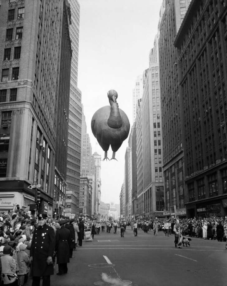 1957 - A giant turkey float squeezes between buildings as the 31st annual Macy's Thanksgiving Day Parade moves down Broadway near 37th Street in New York, Nov. 28, 1957. The parade's first giant balloons debuted in 1927. (AP Photo/John Lindsay, File)