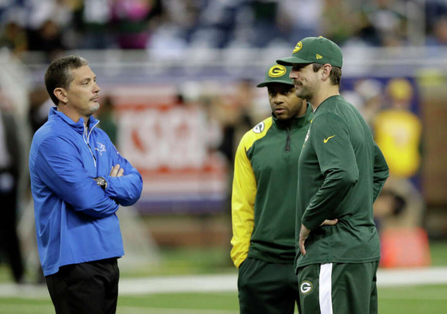 Detroit Lions head coach Jim Schwartz talks with Green Bay Packers wide receiver Randall Cobb, center, and quarterback Aaron Rodgers during a warm up period before an NFL football game at Ford Field in Detroit, Thursday, Nov. 28, 2013. (AP Photo/Carlos Osorio) / AP