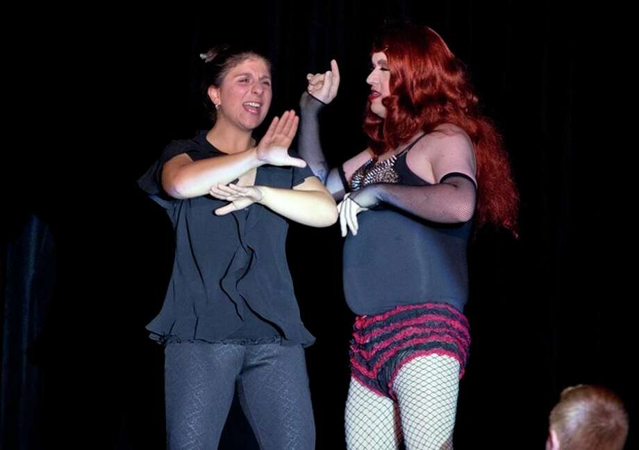 In this Nov. 22, 2013, photo, Holly Maniatty, left, an American Sign Language interpreter, signs during a performance by a contestant in the the Royal Majesty Drag Show and Competition in Portland, Maine. The 33-year-old has become an Internet sensation for the energetic way she uses dance moves, body language and American Sign Language to bring musical performances alive for those who can't hear. (AP Photo/Robert F. Bukaty) / AP