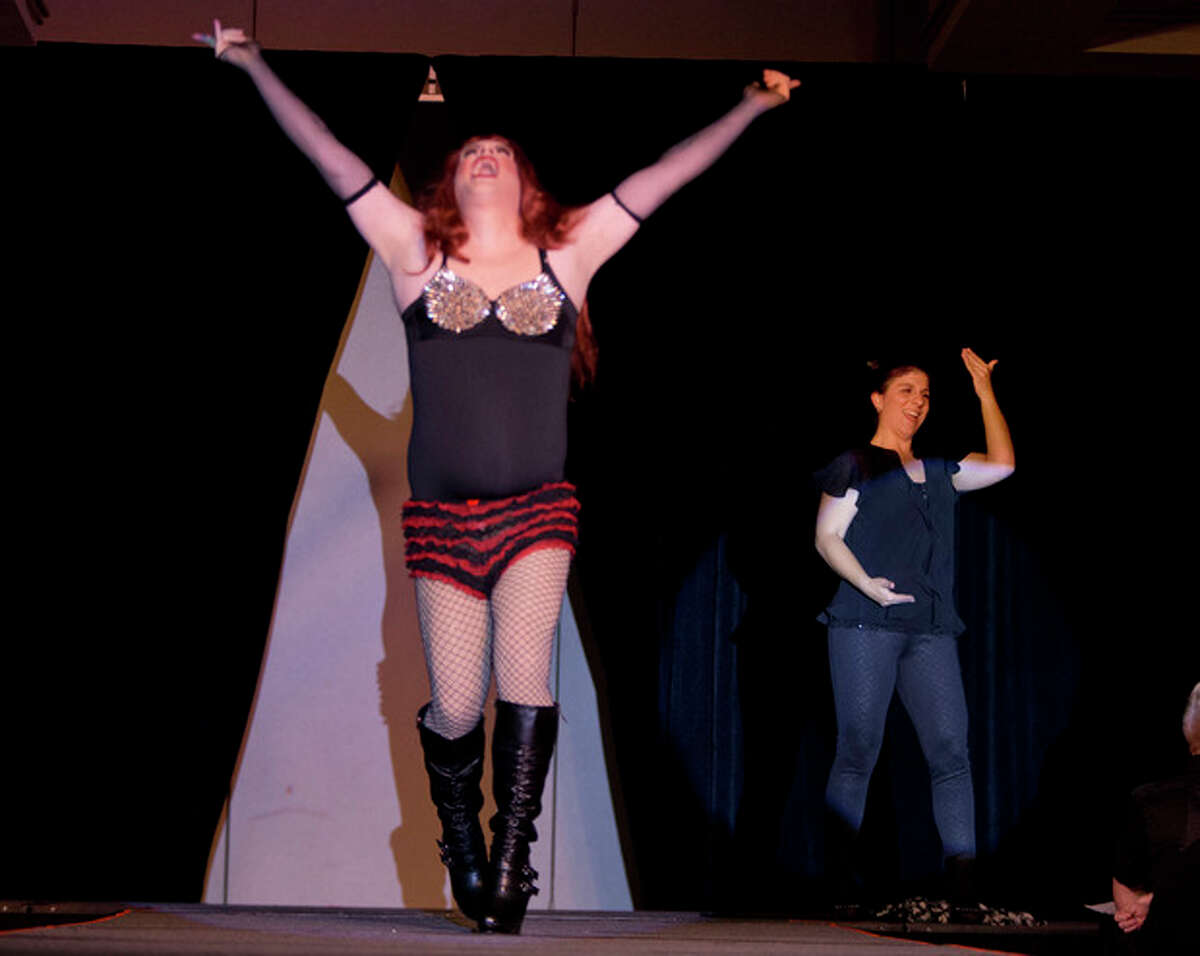 In this Nov. 22, 2013, photo, Holly Maniatty, right, an American Sign Language interpreter, signs during a performance by a contestant in the the Royal Majesty Drag Show and Competition in Portland, Maine. Maniatty has worked with several big-names performers such as Wu Tang Clan, Jay-Z, and Phish. (AP Photo/Robert F. Bukaty)