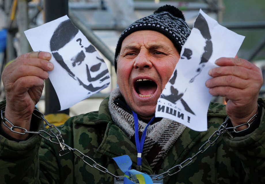 "A demonstrator holds a torn portrait of Ukrainian President Viktor Yanukovych and shouts ""Coward!"" during a rally in support of Ukraine's integration with the European Union in the center of Kiev, Ukraine, Friday, Nov. 29, 2013. Yanukovych said last week that he wouldn't sign the pact at an EU summit on Friday in Vilnius, Lithuania. The European Union extended its geopolitical reach eastward on Friday by sealing association agreements with Georgia and Moldova, but blamed Russia for missing out on a landmark deal with Ukraine. (AP Photo/Sergei Grits) / AP"