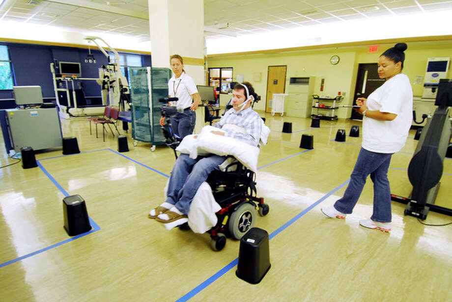 This undated handout photo provided by the Shepherd Center shows Jason DiSanto navigating an obstacle course in an electric-powered wheelchair by issuing commands with a magnetic tongue piercing. The 50-meter-long course, at the Shepherd Center in Atlanta, Ga., included 13 turns and 24 obstacles, requiring tongue drive users to make U-turns, move in reverse and negotiate a loop. (AP Photo/Georgia Tech, Gary Meek) / Shepherd Center
