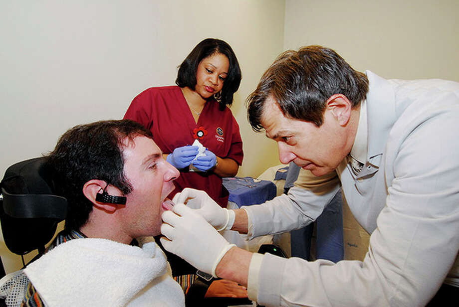 This undated handout photo provided by the Shepherd Center shows Jason DiSanto, left, receiving a tongue piercing at Georgia Tech in Atlanta. An experimental device is letting paralyzed people drive wheelchairs simply by flicking their tongue in the right direction. The Tongue Drive System was developed at Georgia Tech and tested at Shepherd Center in Atlanta. (AP Photo/Georgia Tech, Gary Meek) / Shepherd Center