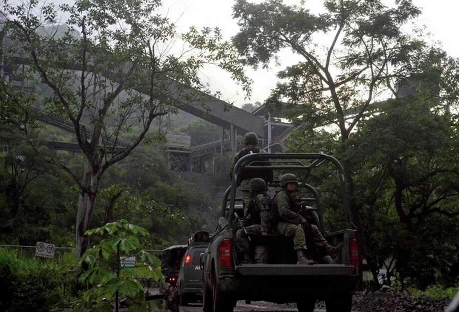 In this Aug. 14, 2013 photo, Mexican army soldiers enter the iron ore mine in the town of Aquila, Mexico. A resident of Aquila, said that since 2012, the Knights Templar cartel demanded residents hand over part of the royalty payments from the local iron ore mine operated by Ternium, a Luxembourg-based consortium. Mexican drug cartels long ago moved into oil theft, pirated goods, extortion and kidnapping, but it still came as a shock this month when federal officials revealed the gangs have broadened the scope and sophistication of their economic empires by entering the country's lucrative mining industry, exporting iron ore to Chinese and other foreign mills. (AP Photo/Agencia Esquema) / Agencia Esquema