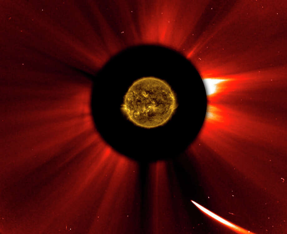 In a composite image provided by NASA, Comet ISON nears the sun in an image captured at 10:51 a.m. Eastern Standard Time on Thursday, Nov. 28, 2013. The sun was imaged by NASA's Solar Dynamics Observatory, and an image from ESA/NASA's Solar and Heliospheric Observatory shows the solar atmosphere, the corona. Scientists are studying spacecraft images to find out whether a small part ISON survived its close encounter with the sun. (AP Photo/ESA&NASA SOHO/SDO) / NASA