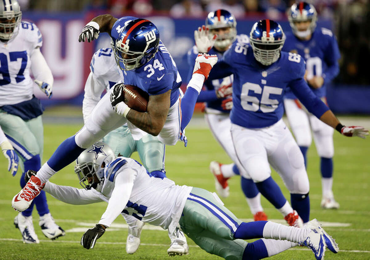 New York Giants running back Brandon Jacobs (34) leaps over Dallas Cowboys strong safety J.J. Wilcox, bottom, during the second half of an NFL football game, Sunday, Nov. 24, 2013, in East Rutherford, N.J. (AP Photo/Seth Wenig)