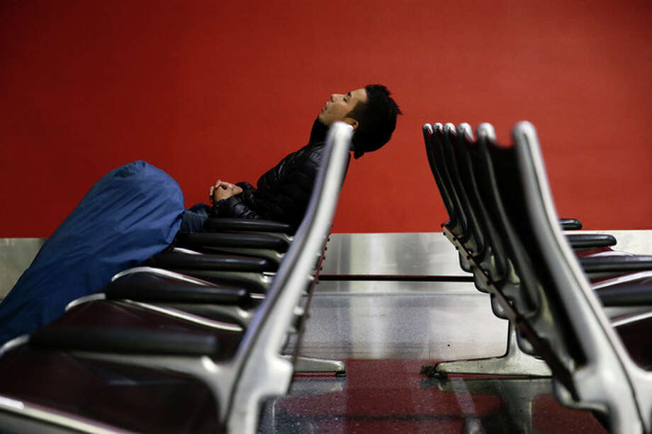 A man sleeps at the Los Angeles International Airport on Wednesday, Nov. 27, 2013, in Los Angeles. More than 43 million people are to travel over the long holiday weekend, according to AAA. (AP Photo/Jae C. Hong) / AP