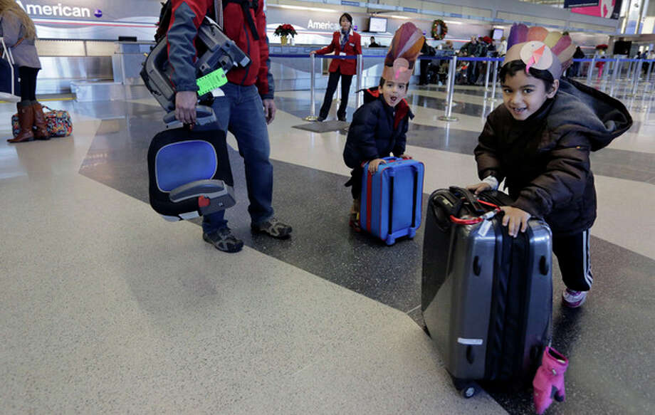 With turkey themed hats, 5-year-old Rishi, and 3-year-old Ravi Chandra wheel their suitcases through terminal three Wednesday, Nov. 27, 2013, at O'Hare International airport in Chicago as they head to Austin, Texas with their parents. While the morning commute at O'Hare is running smoothly, a wall of storms packing ice, sleet and rain heading for the east coast and the north east could upend holiday travel plans as millions of Americans take to the roads, skies and rails Wednesday for Thanksgiving. (AP Photo/M. Spencer Green) / AP