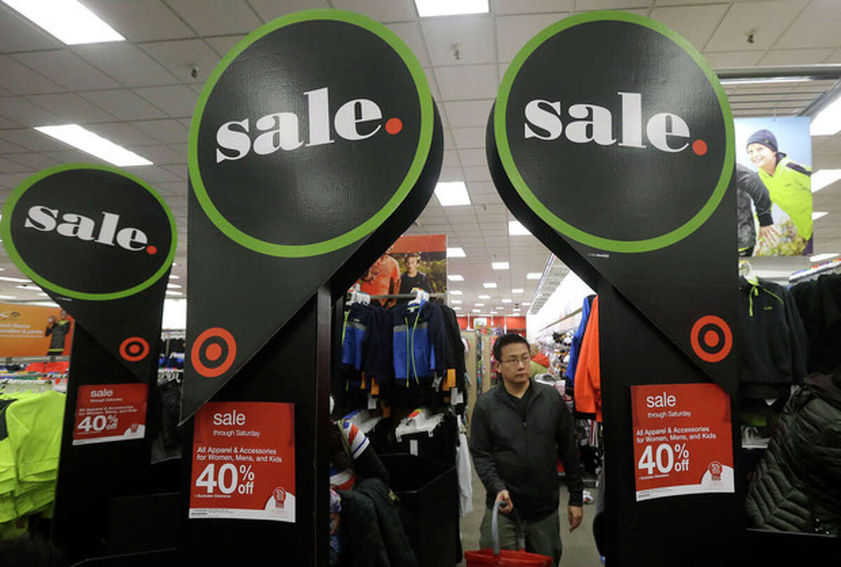 A man walks under sale signs at a Target Store in Colma, Calif., Thanksgiving Day, Thursday, Nov. 28, 2013. Instead of waiting for Black Friday, which is typically the year's biggest shopping day, more than a dozen major retailers opened on Thanksgiving day this year. (AP Photo/Jeff Chiu)